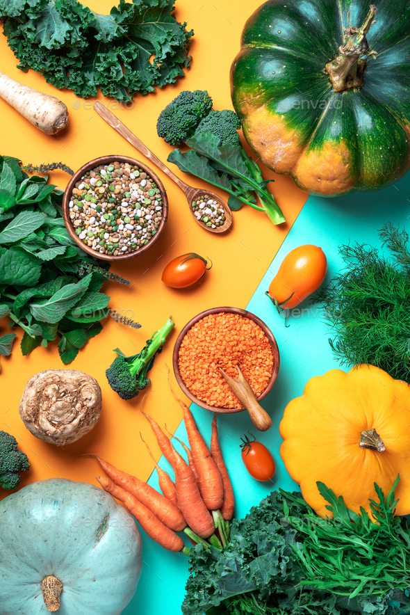Organic vegetables, lentils, beans, raw ingredients for cooking on trendy yellow and green - Stock Photo - Images