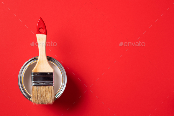 Brush and open paint can on trendy red background. Top view, copy space. Appartment renovation - Stock Photo - Images