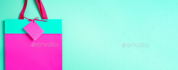 Top view of turquoise and pink paper shopping bag on trendy green background. Copy space. Gift - Stock Photo - Images