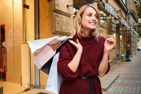 Cheerful blond girl in knitted sweater with shopping bags happily looking away on city street - Stock Photo - Images