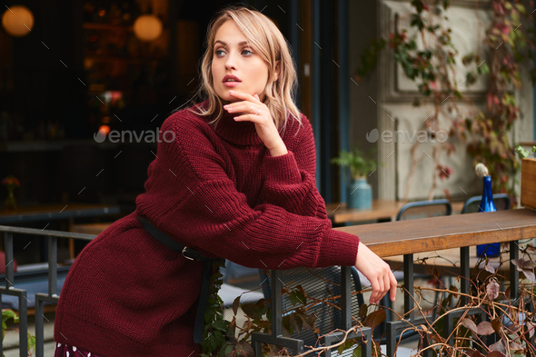 Attractive blond girl in knitted sweater thoughtfully looking away outdoor - Stock Photo - Images