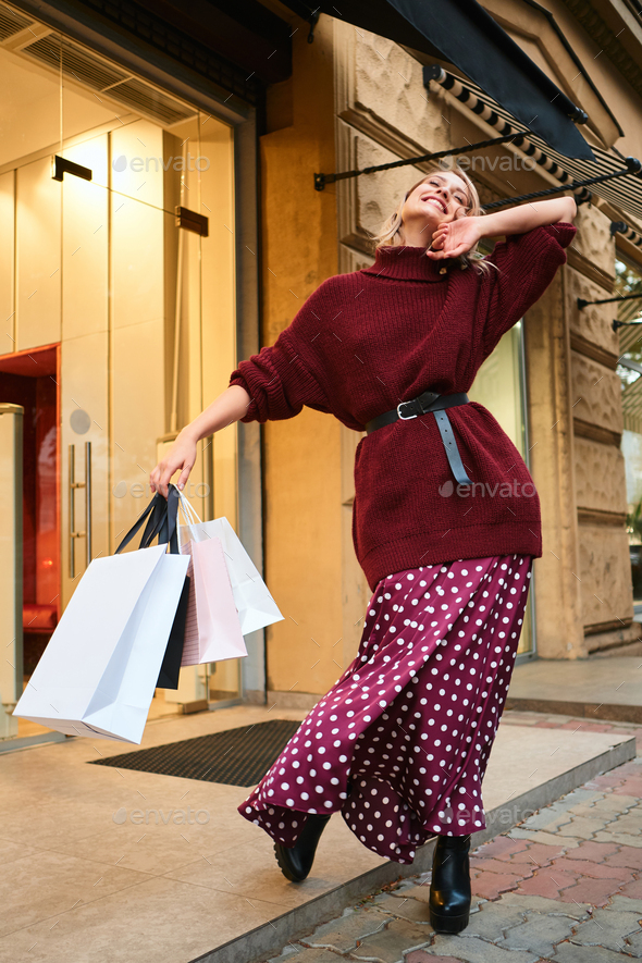 Pretty cheerful stylish blond girl with shopping bags rejoicing after shopping outdoor - Stock Photo - Images