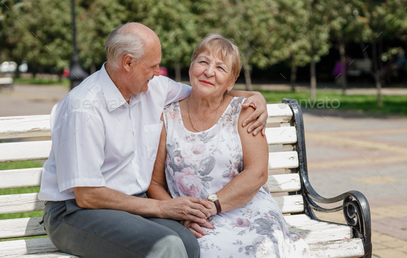 Old man and old woman are sitting lovely together on the bench in a park on a warm day - Stock Photo - Images