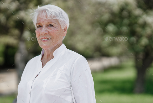 Smiling elegant elderly gray-haired woman in the white shirt is standing in a park on a warm sunny - Stock Photo - Images
