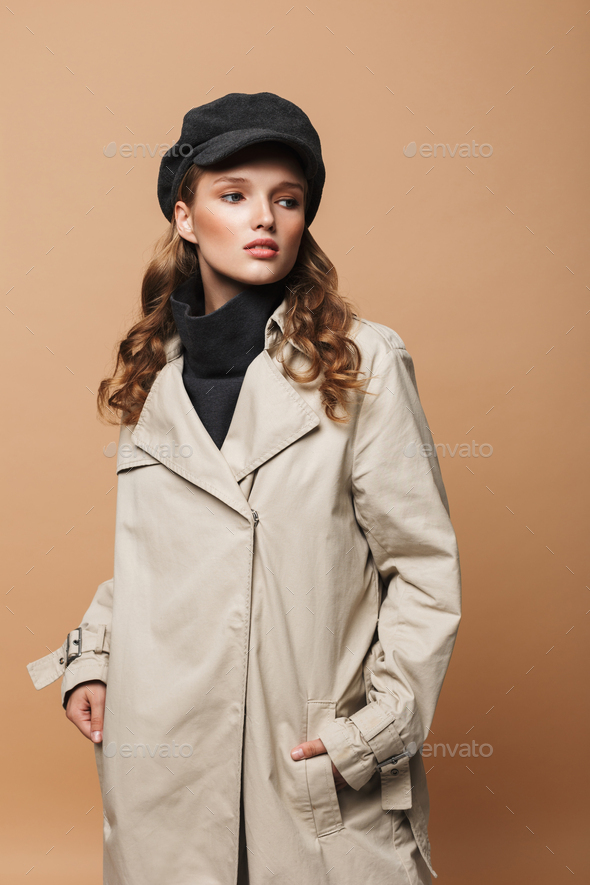 Beautiful girl with wavy hair in trench coat and cap holding hands in pockets over beige background - Stock Photo - Images