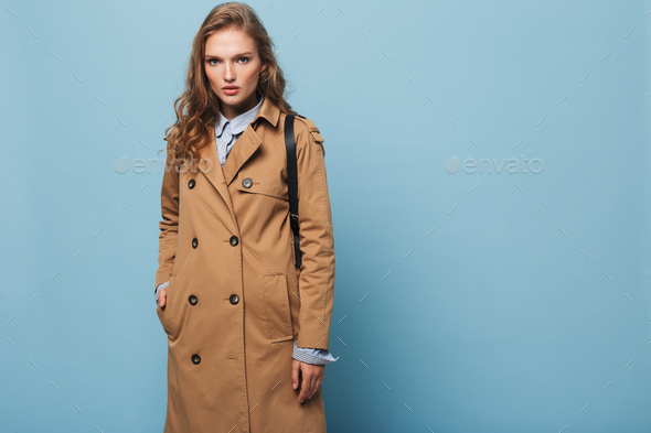 Young model with wavy hair in trench coat thoughtfully looking in camera over blue background - Stock Photo - Images