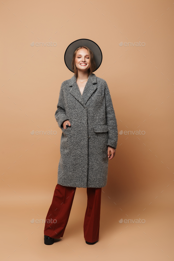 Attractive smiling woman with hat in gray coat and wide pants dreamily closing eyes at studio - Stock Photo - Images