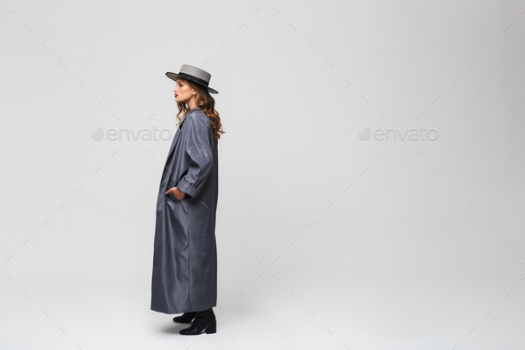 Young woman in hat and cloak holding hand in pocket looking aside over gray background - Stock Photo - Images