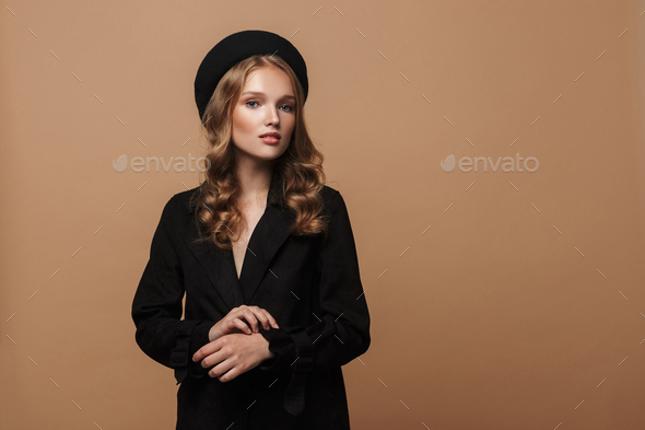 Beautiful woman with wavy hair in black coat and beret dreamily posing over beige background - Stock Photo - Images