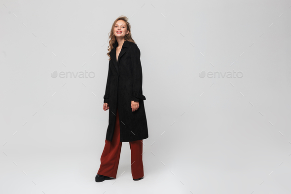 Stylish smiling woman in black coat and red wide trousers joyfully looking in camera at studio - Stock Photo - Images