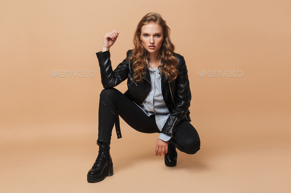 Model with wavy hair in black leather jacket intently looking in camera over beige background - Stock Photo - Images