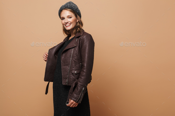 Young cheerful model in hat, leather jacket and black dress happily looking in camera - Stock Photo - Images