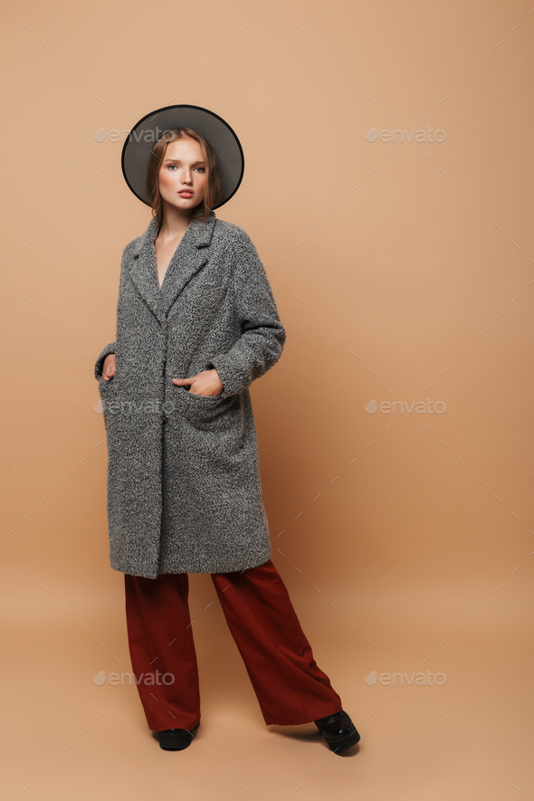 Stylish model with hat in gray coat and wide pants posing over beige background - Stock Photo - Images