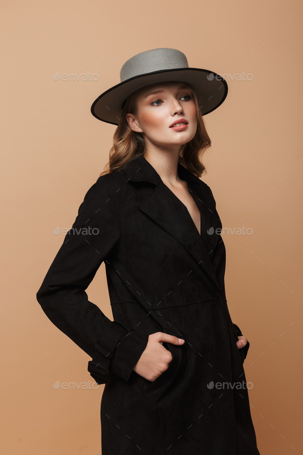 Gorgeous woman in black coat and gray hat dreamily looking aside over beige background - Stock Photo - Images