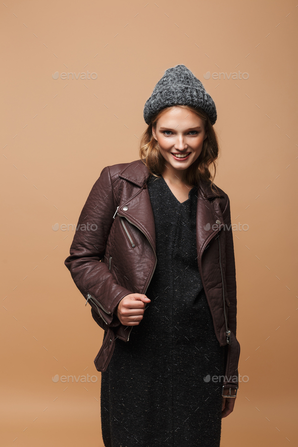 Young beautiful joyful woman in hat, leather jacket and black dress happily looking in camera - Stock Photo - Images