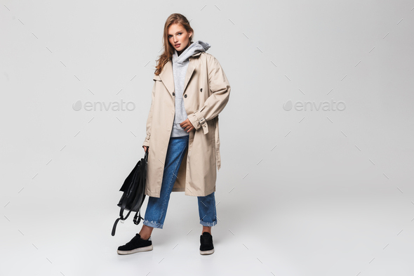 Young gorgeous woman in trench coat and jeans holding black backpack in hand - Stock Photo - Images