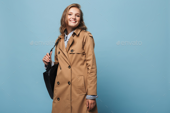 Beautiful smiling girl with wavy hair in trench coat with black backpack happily looking in camera - Stock Photo - Images