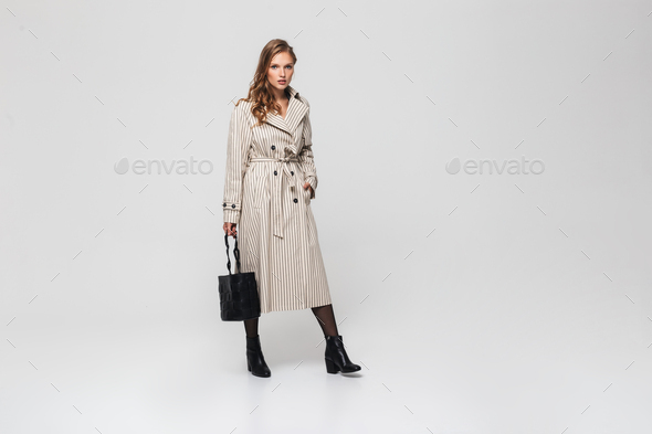 Beautiful woman with wavy hair in striped coat holding black bag thoughtfully looking in camera - Stock Photo - Images