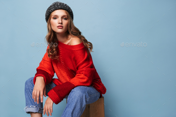 Young attractive woman with wavy hair in hat and red sweater thoughtfully looking in camera - Stock Photo - Images