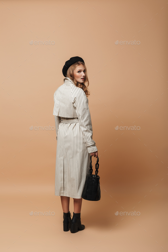 Young attractive woman in coat and black hat holding bag thoughtfully looking in camera from back - Stock Photo - Images