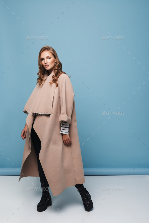 Young beautiful woman with wavy hair in beige coat and black boots dreamily looking in camera - Stock Photo - Images