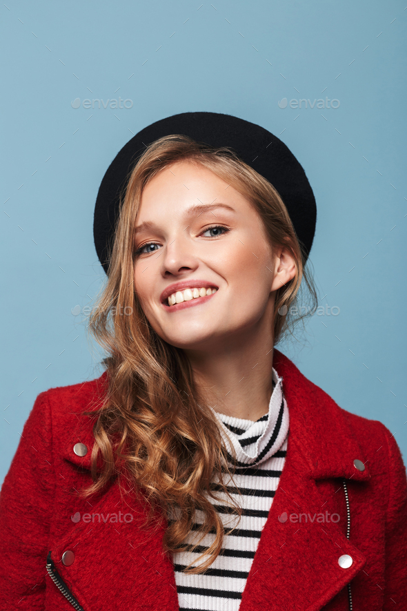 Young smiling woman with wavy hair in beret and red jacket happily looking in camera - Stock Photo - Images
