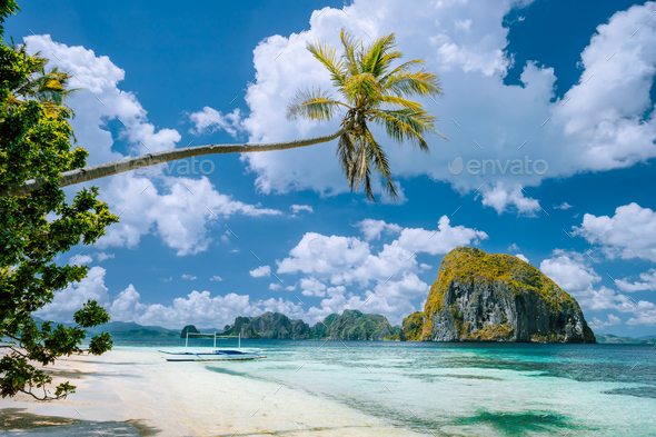 El Nido, Palawan, Philippines. Tropical scenery of exotic beach with palm tree, boat on the sandy - Stock Photo - Images