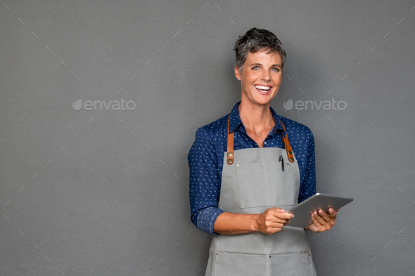 Mature woman in apron holding digital tablet - Stock Photo - Images