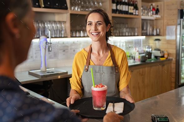 Smiling waitress serving strawberry smoothie - Stock Photo - Images