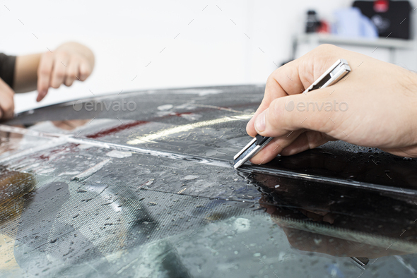 Applying a protective film with tools for work. Car detailing - Stock Photo - Images