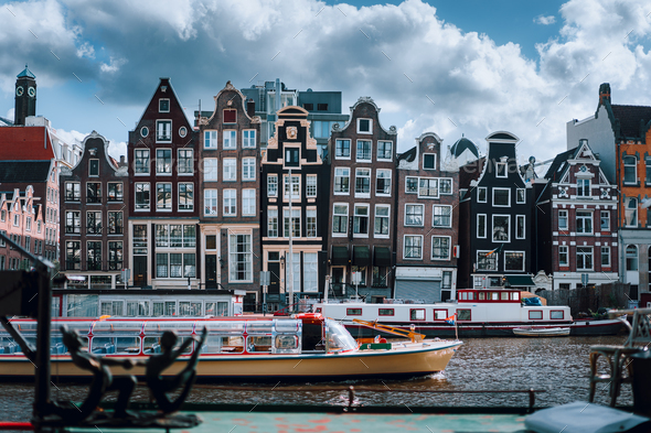 Amsterdam canal Singel with typical dutch houses and houseboats with beautiful cloudscape in - Stock Photo - Images