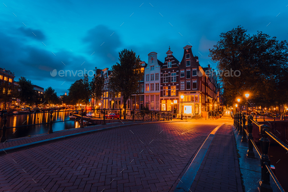 Amsterdam illuminated bridge with typical dutch houses in evening blue hour lights, Holland - Stock Photo - Images