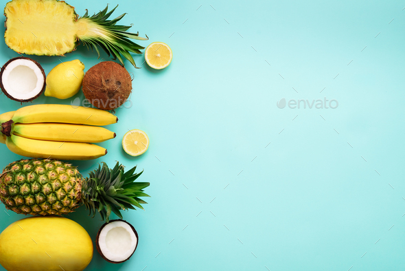 Fresh organic yellow fruits over blue background. Monochrome concept with banana, coconut, pineapple - Stock Photo - Images