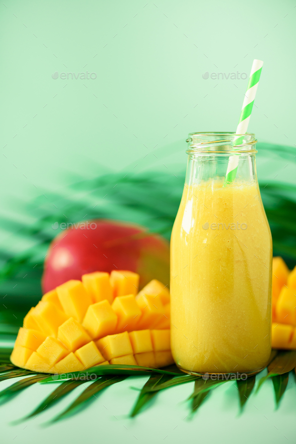 Delicious juicy smoothie with orange fruit and mango on turquoise background. Copy space. Pop art - Stock Photo - Images