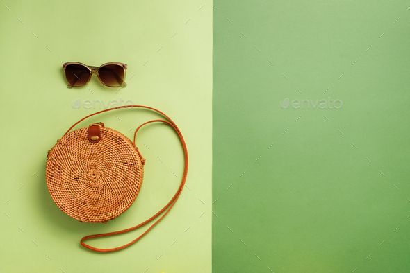 Round rattan bag, sunglasses on green background. Banner. Top view with copy space. Trendy bamboo - Stock Photo - Images