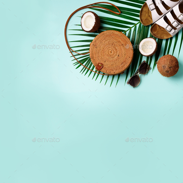 Round rattan bag, coconut, birkenstocks, palm branches, sunglasses on blue background. Square crop - Stock Photo - Images
