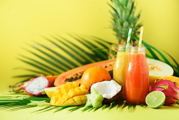 Juicy papaya and pineapple, mango, orange fruit smoothie in two jars on yellow background. Detox - Stock Photo - Images