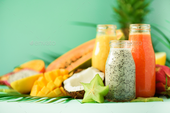 Papaya, dragon fruit, pineapple, mango smoothie in jars on turquoise background. Detox, vegan diet - Stock Photo - Images
