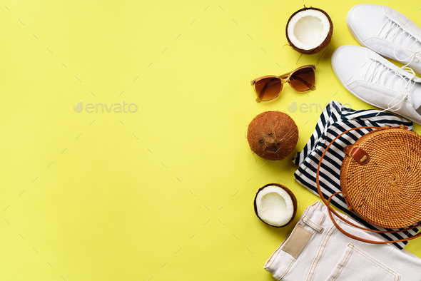 Female white sneakers, jeans, striped t-shirt, rattan bag, coconut and sunglasses on yellow - Stock Photo - Images
