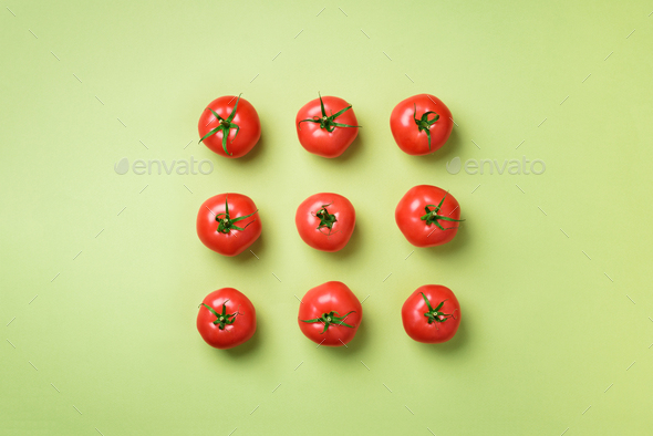 Creative pattern of red tomatos on green background. Top view. Copy space. Minimal design - Stock Photo - Images