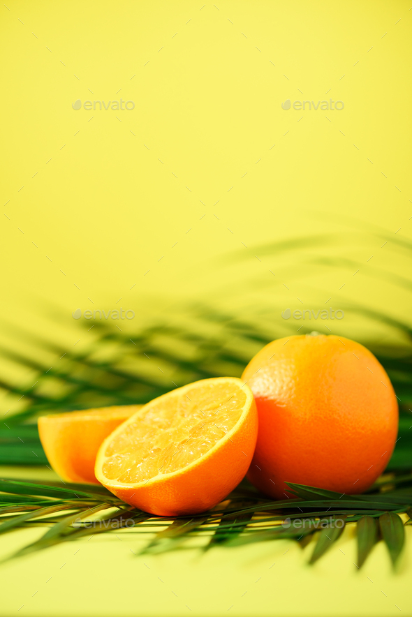 Orange fruit over tropical green palm leaves on yellow background. Copy space. Pop art design - Stock Photo - Images