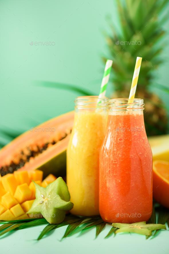 Juicy papaya and pineapple, mango, orange fruit smoothie in two jars on turquoise background. Detox - Stock Photo - Images