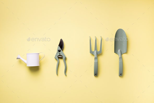 Gardening tools and utensils on yellow background. Top view with copy space. Pruner, rake, shovel - Stock Photo - Images