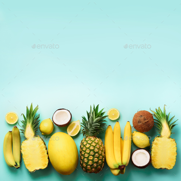 Fresh organic yellow fruits over blue background. Square crop. Monochrome concept with banana - Stock Photo - Images