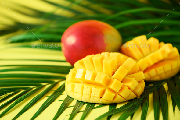 Exotic mango fruit over tropical green palm leaves on yellow background. Copy space. Pop art design - Stock Photo - Images