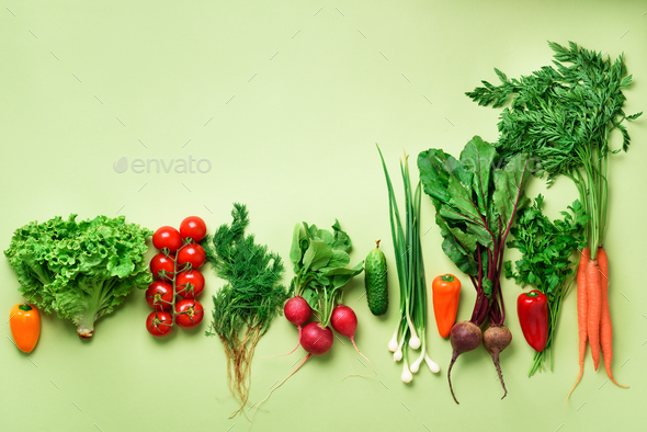 Organic vegetables and garden tools on green background with copy space. Top view of carrot, beet - Stock Photo - Images