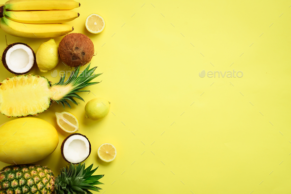 Fresh organic yellow fruits over sunny background. Monochrome concept with banana, coconut - Stock Photo - Images