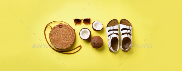 Stylish rattan bag, coconut, birkenstocks, palm branches, sunglasses on yellow background. Banner - Stock Photo - Images