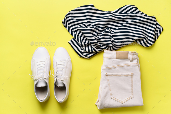 Female white sneakers and jeans, striped t-shirt on yellow background with copy space. Top view - Stock Photo - Images