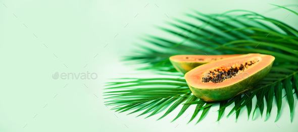 Exotic papaya fruit over tropical green palm leaves on turquoise background. Copy space. Pop art - Stock Photo - Images